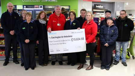 Staff at Budgens of Holt presenting East Anglian Air Ambulance Norfolk fundraising officer Jamie Edg