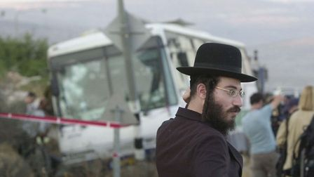 An Israeli orthodox Jewish man looks on as emergency workers work near a destroyed bus, at the scene