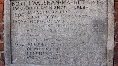 The old Market Cross history stone at North Walsham that is almost unreadable, and has been replaced