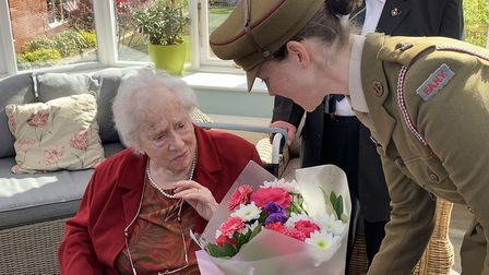 Commander Alex Milne of the FANYs gives flowers to Dorothy Mann, at the presentation of her Légion d