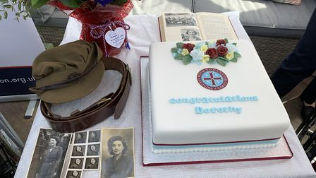 Photos, a cake and a wartime hat and belt at the presentation of Dorothy Mann's Légion d'honneur at