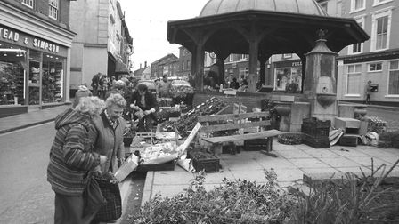 Two ladies enjoying a chat whilst looking at Christmas trees and holly in the Market Place in North
