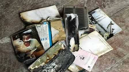 Some of the charred remains of family photographs after the fire. Picture: Ella Wilkinson