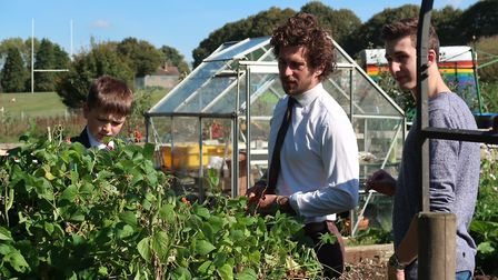 Matt Willer, centre, inspects what's growing at Reepham High School and College's Allotment Project.