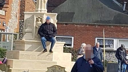 A man was photographed seated on the town's war memorial during the Cromer Vintage 1960s Festival on