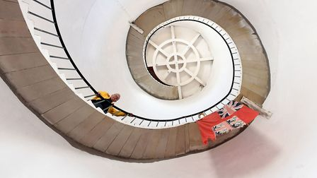Friends of Happisburgh Lighthouse volunteer Stephen Burke on the 96 step stone staircase featuring a