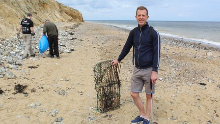 Alex Segens with a lobster crate he found during a beach clean on East Runton beach. It's the work o