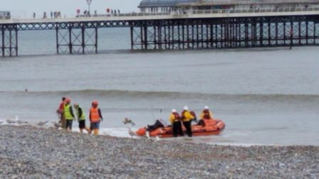 Emergency service workers loading a boat with firefighting equippment to tackle the blaze on the cli