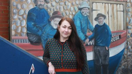Sheringham Museum manager Lisa Little standing in front of a mural featuring her great-great grandfa