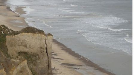 Part of a cliff has fallen to the beach at Trimingham.This picture shows the cliff before it fell. P
