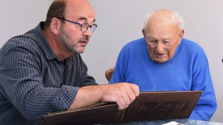 World War Two veteran, William 'Billy' Twiddy, looks over the old photographs with Francis Bertrand,