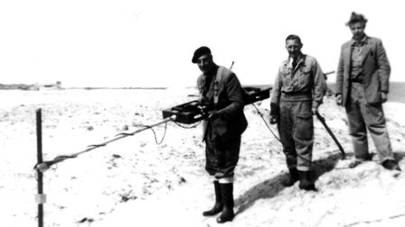 Men using metal detectors to look for mines on the cliffs and beaches after the Second World War at