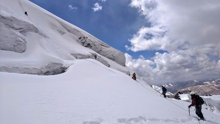 The team climbs over crevasses and snow bridges to the summit of a 'virgin' mountain in Kyrgyzstan.