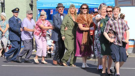 Festival-goers take part in a conga around Market Place, accompanied by songs from 1980s icon David