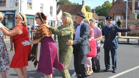 Festival-goers take part in a conga around Holt market place, accompanied by songs from 1980s icon D