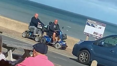 Two men on mobility scooters engaged in a good-natured bumper battle on the seafront in Walcott, Nor
