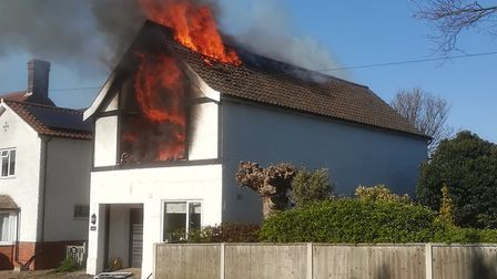 Flames pouring from the roof of the house in Station Road, West Runton in April. Picture: DEAN McCRO