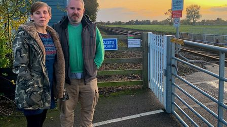 Michelle Johns and Andy Purser next to the railway crossing outside their home in Church Lane, Tunst