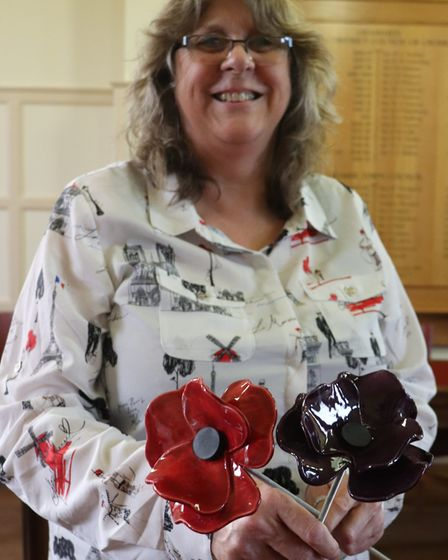 Cromer Town Council town clerk Julie Chance holding a red and purple poppy on their metal stems. Tho
