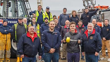 Crewman Lewis Gray and friend Charlie Graham-Ward presenting the beacon to the crew of RNLI Sheringh