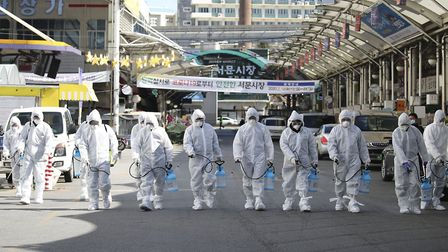 Workers wearing protective gear spray disinfectant as a precaution against coronavirus at a market i