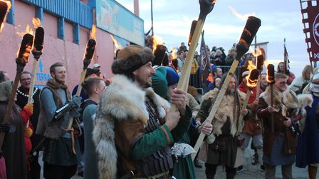 Flame torch-carrying Vikings get set for the ceremonial boat-burning on the beach. Photo: KAREN BETH
