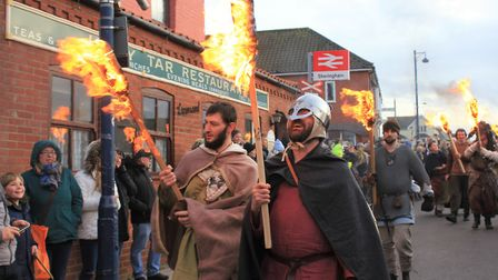 Flame torch-wielding warriors march down the high street at Sheringham's Scira Viking Festival final