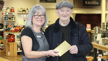 Barry Williams getting a cheque from staff member Nettie Bartle as part of Bakers & Larners of Holt