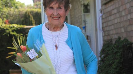 Former Second World War nurse Gwyneth Denton, 97, with a bouquet of flowers presented to her on her
