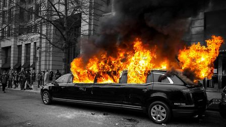 A limousine on fire during a demonstration
