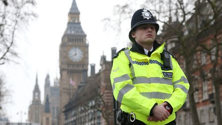 A police officer close to New Scotland Yard in London, after seven people were arrested in raids in