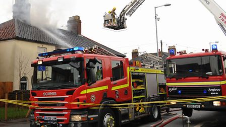 Firefighters tackle the fire in the roof of four houses in Magpie Road. Picture: Denise Bradley