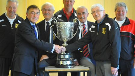 Acle United chairman John Goward receives the Sterry Cup from Anglian Combination chairman Graham Ju