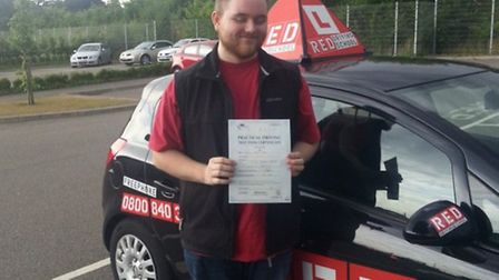 Charlie Storey proudly holds his driving test certificate after overcoming anxiety; Photo credit: Su