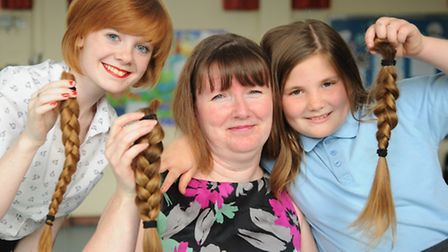 Sisters Mollie, 16, and Lilly Walker, 9, and teacher Mandy Power, have their long hair cut short in