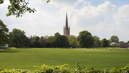 Cricketers enjoy a game in the sun on the green in front of Norwich Cathedral