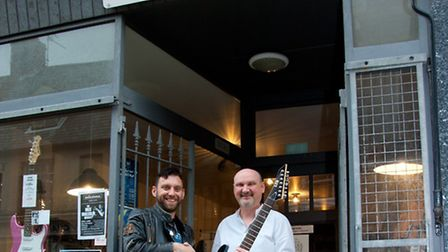 Pete Lister, owner of Listers Guitars in Lowestoft, gives Jim Marten a guitar to be auctioned off to