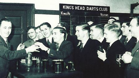 Surrounded by players, King's Head landlord Billy Goffin hands club captain Ken Percival a drink at