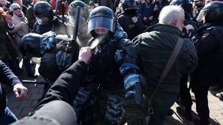 A man blasts a policeman with pepper spray during an anti-corruption protest in Moscow, Russia, on M