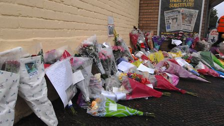Floral tributes and photographs in memory of Lisa Jermy outside the Norwich shop where she died afte