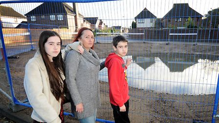 Tracey Clayton and her children, Darcey, 14 and Robson, 13, with the drainage basin on Badgers Brook