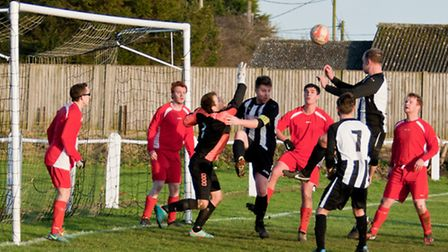 Jamie Buhlemann rises to meet George Hutton's corner to open his scoring account in Swaffham Reserve