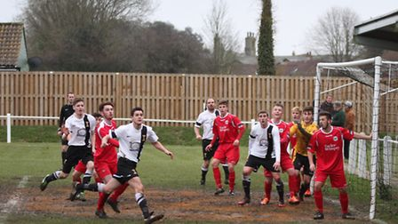 Mark Allibone keeps his eye on the ball during Swaffham's (white) 3-0 win against Needham Market Res