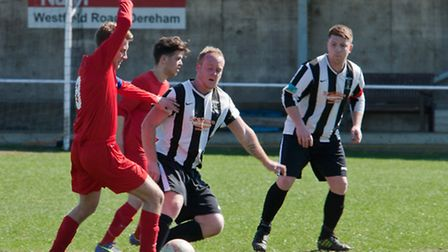 Action from Swaffham Town Reserves' 1-0 loss at Easton (red), Aaron Marsh challenging as skipper and
