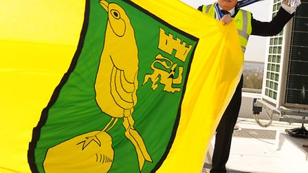 Ipswich fan, Graham Wray, NPS facilities manager at County Hall, has to raise the Norwich City flag