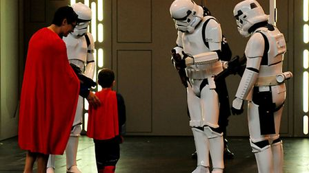 Comic Con enthusiasts a young Superman with mum meet Star Wars during The MCM Birmingham Comic Con a