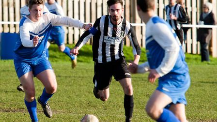 Action from Swaffham Town Reserves against Loddon United Reserves (blue) at Shoemakers Lane, captain