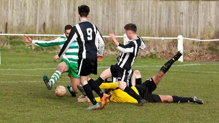 Swaffham Reserves Harry Porter slots home to open his account against Beccles Caxton. Picture: Eddie