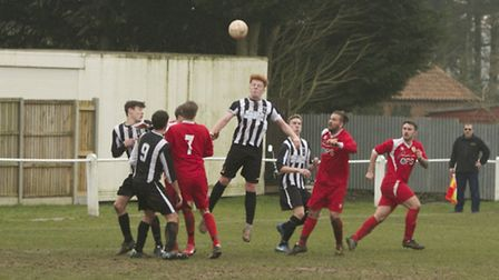 Action from Swaffham Town Reserves' 2-1 loss to Hemsby at Shoemakers Lane, Dan Farr rises to meet th