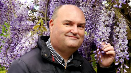 Terry Bane, Ambassador of Norwich in Bloom, admiring Wisteria. Photo: Submitted